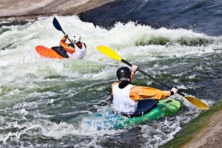 Zwei aktive Kajakfahrer rollen und Surfen im rauen Wasser Standard-Bild - 19943971