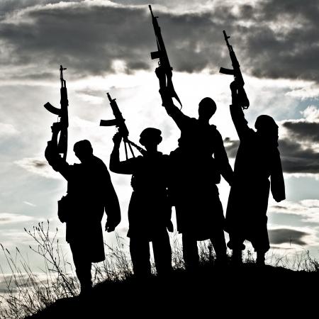 silhouette soldat: Silhouette de plusieurs militants musulmans avec des fusils