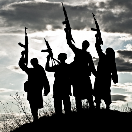 Silhouette of several muslim militants with rifles Stock Photo