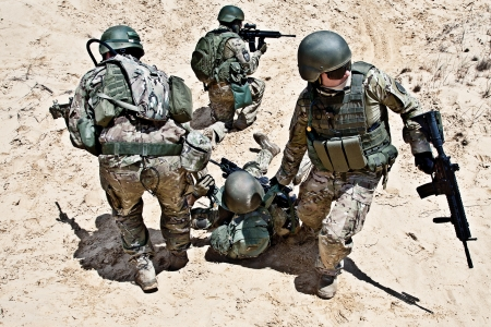 Squad of soldiers evacuate the injured fellow in arms in the desert Stock Photo