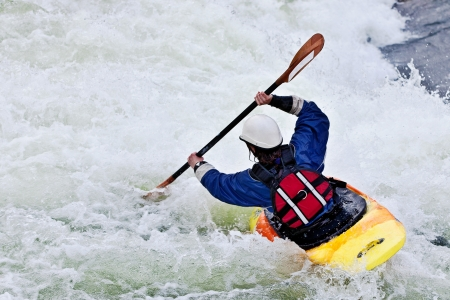 kayak: an active female kayaker rolling and surfing in rough water Stock Photo
