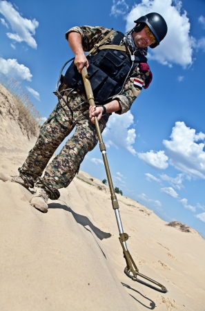 metal detector: iraqi soldier in the desert with army metal detector