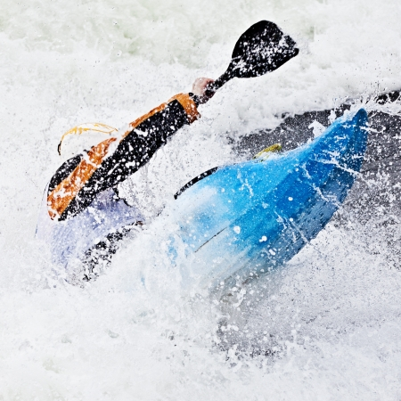 paddling: an active male kayaker rolling and surfing in rough water