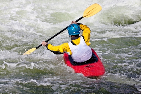 an active male kayaker rolling and surfing in rough water