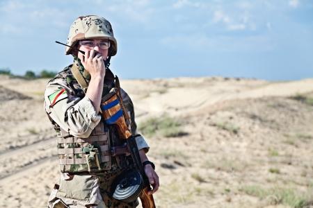Iraakse soldaat in de woestijn praten draagbare radiozender Stockfoto