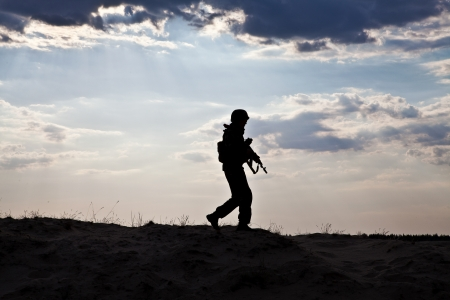 soldier silhouette: Silhouette of young soldier in military helmet against the sun