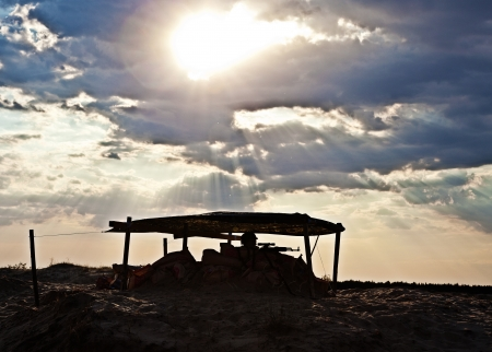 iraq war: Military desert checkpoint with armed sentinel in the sunset Stock Photo