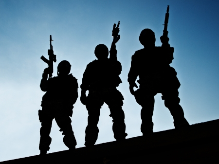Silhouettes of S W A T  officers holding their guns