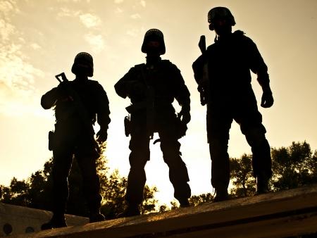 Silhouetten van SWAT officieren die hun geweren Stockfoto