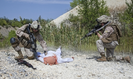 syrian war: Two US marines making a search of killed muslim warrior