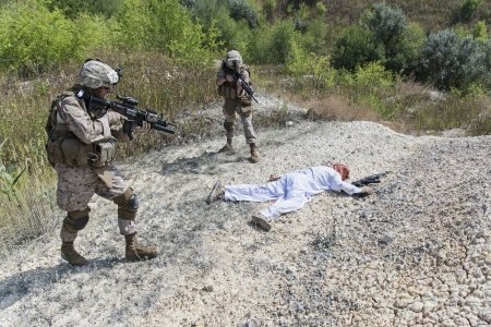 arab spring: Two US marines making a search of killed muslim warrior