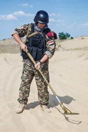 landmine: iraqi soldier in the desert with army metal detector
