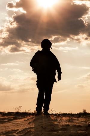 silueta humana: Silueta de joven soldado en el casco militar contra el sol Foto de archivo