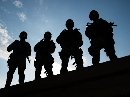 assault forces: Silhouettes of S.W.A.T. officers holding their guns