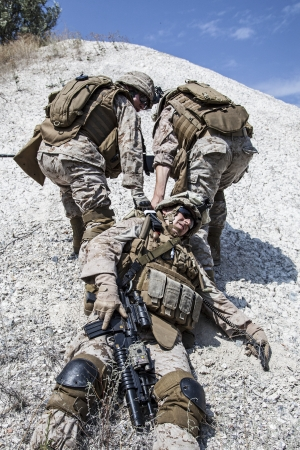US marines evacuate the injured fellow in arms in the mountains Banque d'images