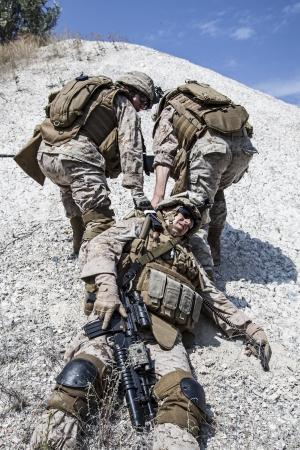 evacuacion: Marines evacuan el compañero herido en los brazos, en las montañas