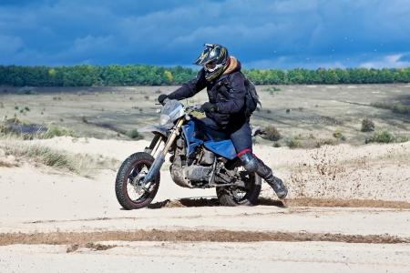 Enduro bike rider driving across the desert photo