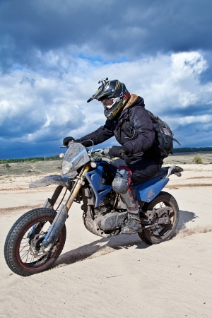 Enduro bike rider driving across the desert photo