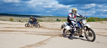 Enduro bike riders driving through the desert photo