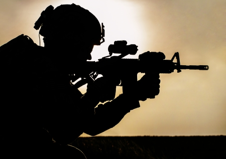militant: Silhouette of young soldier in military helmet against the sun