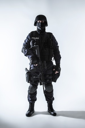 swat teams: Special weapons and tactics team officer with his gun