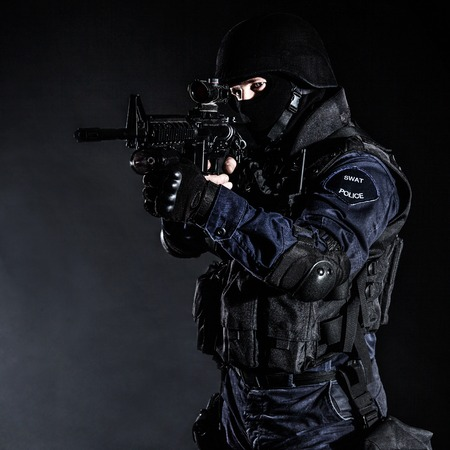 Special weapons and tactics (SWAT) team officer on black  Stock Photo