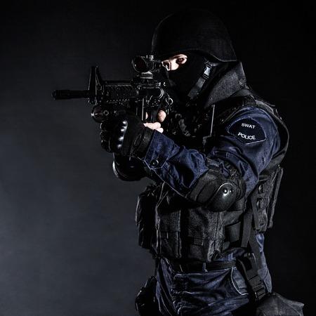 Speciale wapens en tactieken (SWAT) team officier op zwart