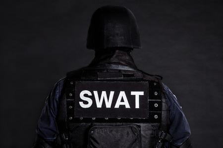 Special weapons and tactics (SWAT) team officer on black shot from behind