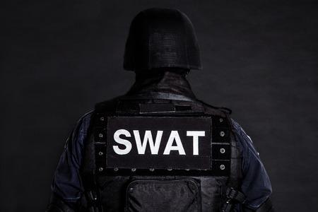 Speciale wapens en tactieken (SWAT) team officier op zwart schot van achter Stockfoto