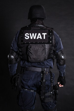 team from behind: Special weapons and tactics (SWAT) team officer on black shot from behind