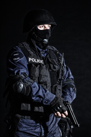 tactical: Special weapons and tactics (SWAT) team officer on black  Stock Photo