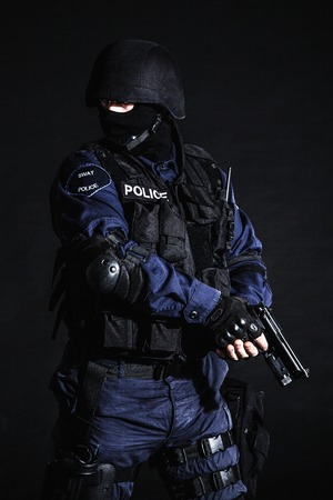 swat teams: Special weapons and tactics (SWAT) team officer on black  Stock Photo