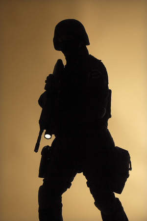 counter terrorism: Special weapons and tactics team  SWAT  officer silouette in the fog