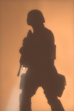 police equipment: Special weapons and tactics team officer silouette in the fog