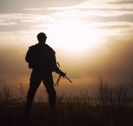 Silhouette of US marine with rifle  against the sunset photo