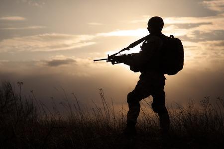 私たちは夕日とライフルを持つ海洋のシルエット