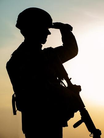 silhouette soldat: Silhouette de soldat am�ricain avec le fusil contre le coucher du soleil Banque d'images
