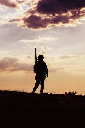 silhouette soldat: Silhouette de soldat américain avec le fusil contre le coucher du soleil Banque d'images