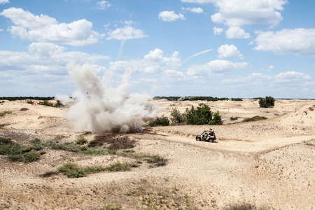 Large explosion near the car with soldiers in the desert photo