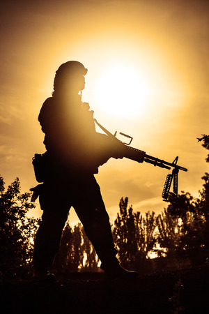 Silhouette of young soldier in military helmet against the sun