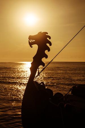 vikingo: Vikingo drakkar en el mar abierto al atardecer