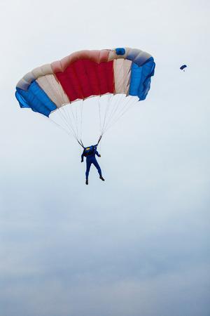 skydive: Male parachutist under a multi-coloured parachute