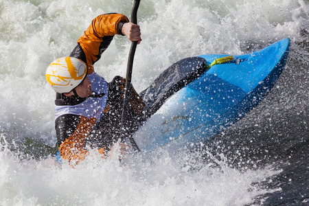kayaker: an active male kayaker rolling and surfing in rough water