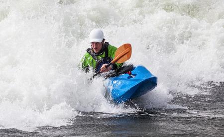 een actieve mannelijke kayaker rollen en surfen in ruwe water