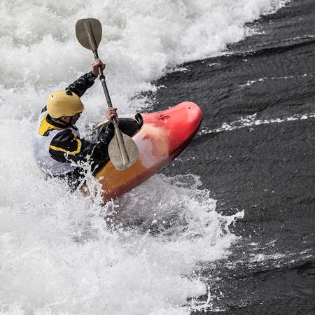 거친 물에 적극적인 남성 카약 롤링 서핑