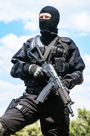 soldier with rifle: Spec ops soldier in black uniform and face mask with his rifle Stock Photo