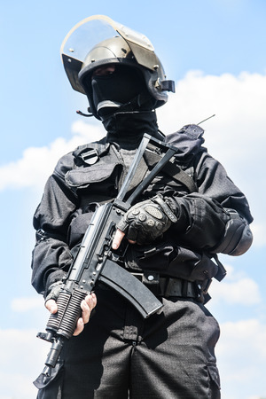 squad: Spec ops soldier in black uniform and face mask with his rifle Stock Photo
