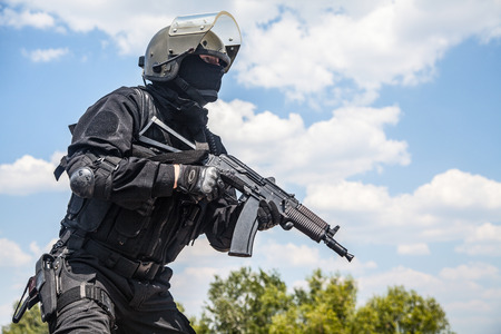 Spec ops soldier in black uniform and face mask with his rifle Stock Photo