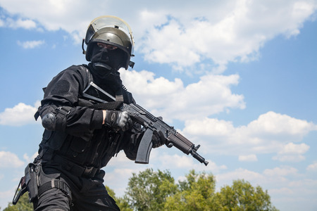 anti terrorist: Spec ops soldier in black uniform and face mask with his rifle Stock Photo