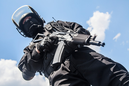 police equipment: Spec ops soldier in black uniform and face mask with his rifle Stock Photo